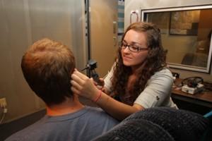 Student examines hearing.