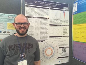 Zach Harris standing next to his poster in Italy.