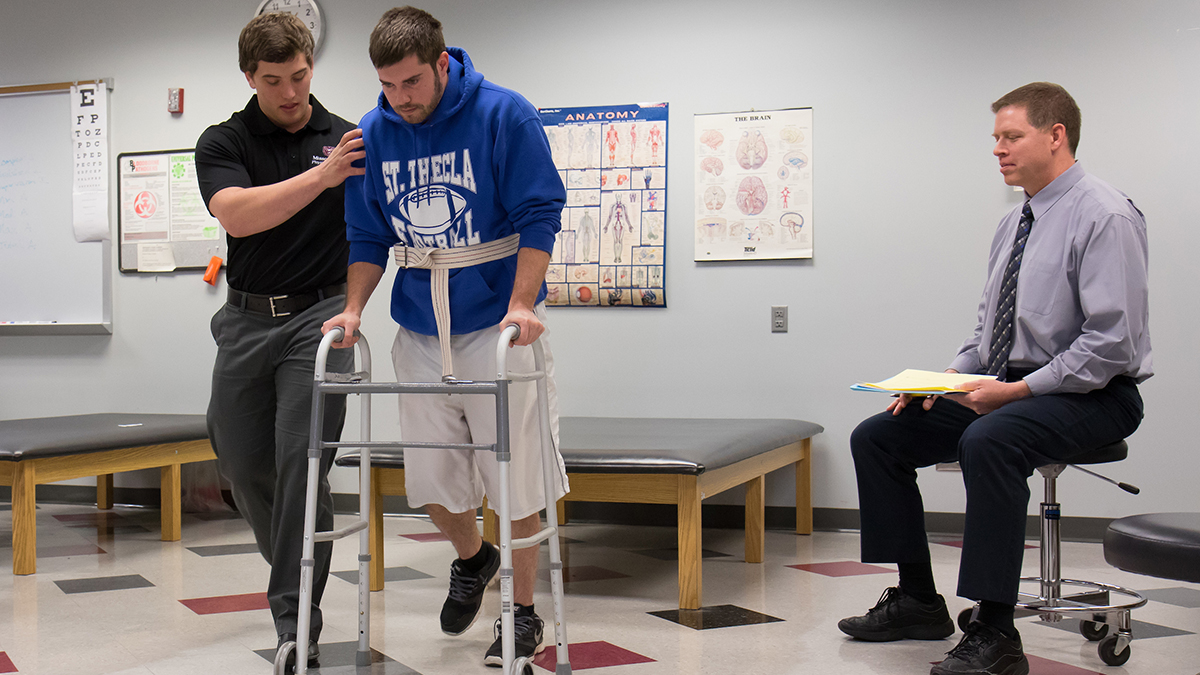 A college student using a walker with assistance