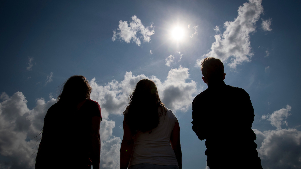 People looking at the sun through solar glasses