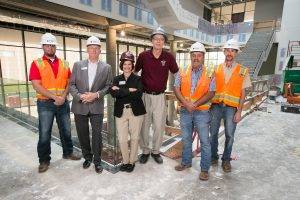 Stephanie Bryant, David Meinert and Dewitt Construction employees inside Glass Hall.