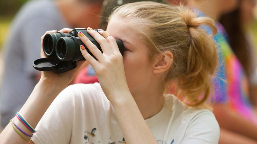 A girl in a white T-shirt looks through binoculars