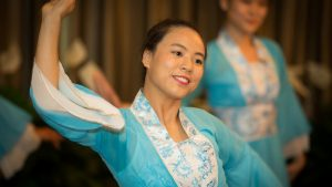 An Asian-American student wearing a teal blue robe dances at Asia Fest 2017