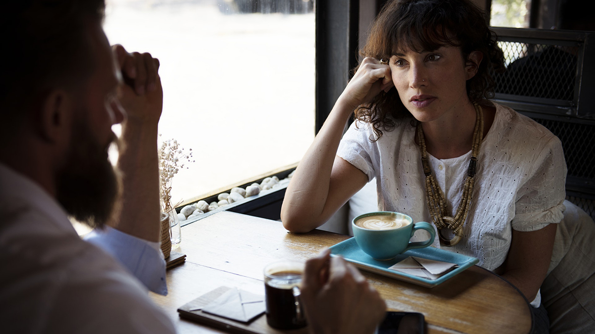 A man and woman having a conversation at a cafe.