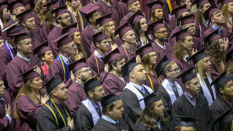 Graduates in maroon robes stand at JQH Arena