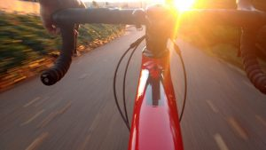 A view of bike handlebars facing a sunset