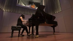 A student plays a Steinway piano in Ellis Hall