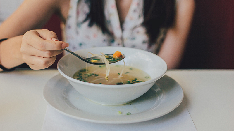 A woman eating a bowl of soup.
