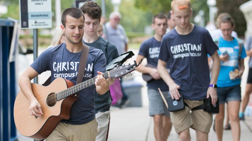 Student strums guitar