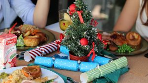 Individuals enjoy a Christmas meal.