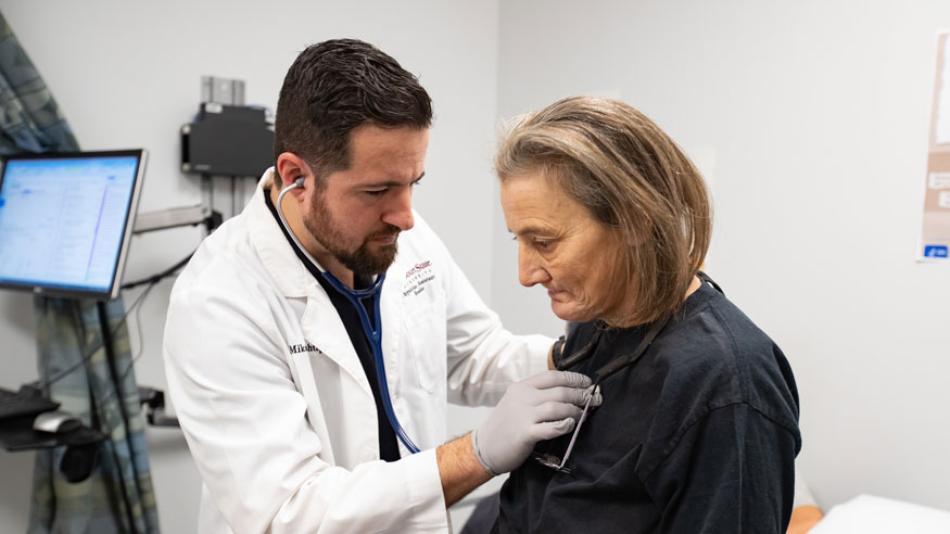 physician uses stethoscope on woman.