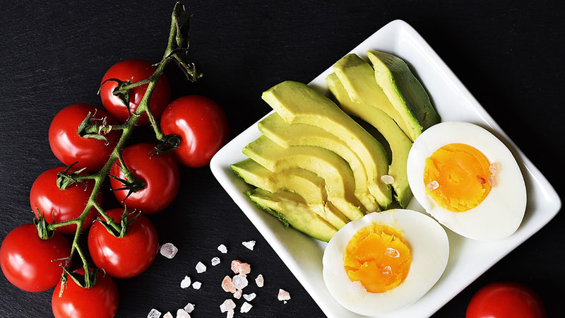 A plate of half boiled egg with some sliced avocados, as well as cherry tomatoes on the side.
