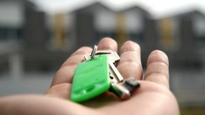 A hand holding keys to a house.