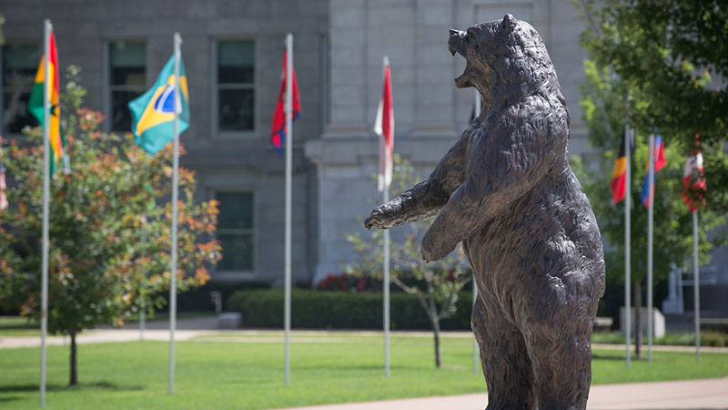 The bear statue and flags on Missouri State's campus.