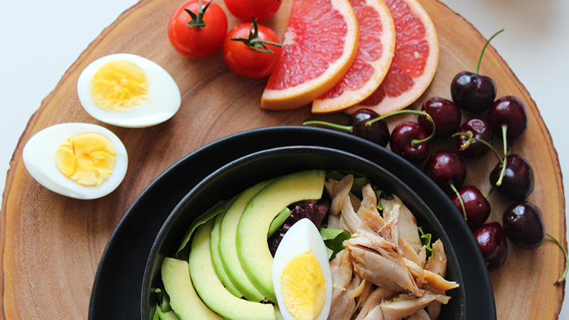 A platter of low-fat food items - chicken salad with sides of tomatoes, cherries and grapefruit.