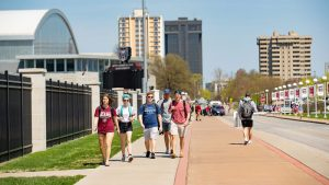 Students walk to class on a sunny spring day on campus.