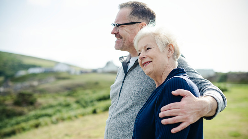 An elderly man with his arm around an elderly woman as they enjoy a scenic view.