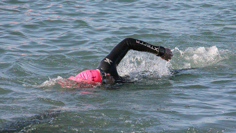 A triathlete swims in the ocean.