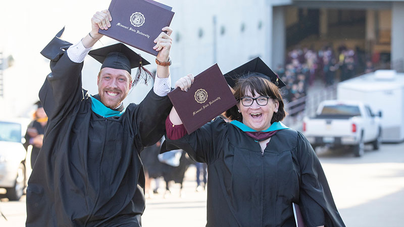 A male and female graduate show hold up their degrees.