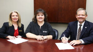 Three people sign documents at a table