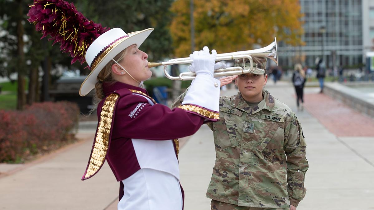 Trumpeter playing Taps as veteran salutes
