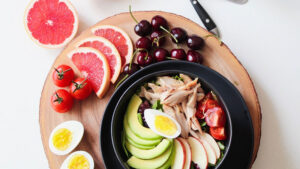 A bowl of chicken salad with cherries, cherry tomatoes, grapefruit and egg on the side.