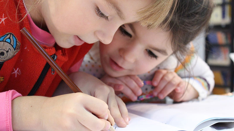 Two young children practice writing and drawing.