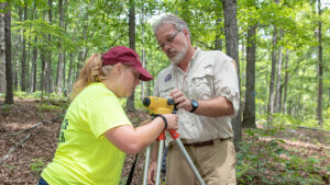 Grace Roman and Bob Pavlowsky set up a surveying tool in the Mark Twain National Forest ching the effects of controlled burning on soil conditions and water quality in the Big Barren River watershed.Jesse Scheve/Mi