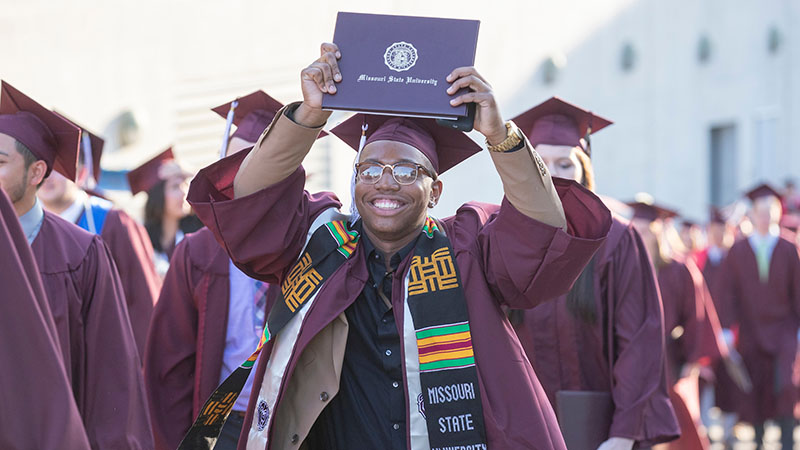 An African American graduate smiles and shows off his degree.