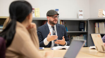 Professor talking with students around a table