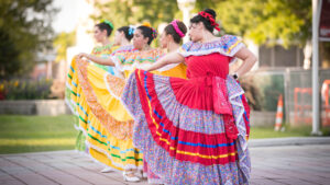 Five women is colorful dresses dancing