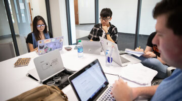 Two male students and one female student studying together.