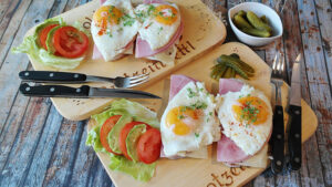 Two platters of eggs, ham and cheese sandwiches with a side of lettuce, tomatoes and dill pickles.