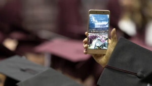 A graduate takes a photo of commencement on his phone.