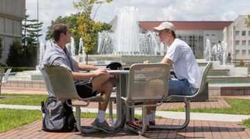 Students talk at an outdoor table.