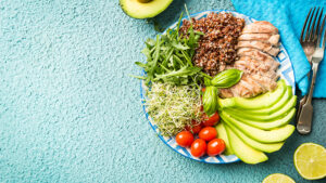 A plate with ingredients of balanced healthy food - quinoa, tomatoes, chicken, avocado and mixed greens.