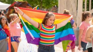 Person holding rainbow flag behind their head