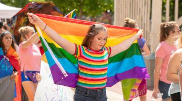 Person holding rainbow flag behind their head