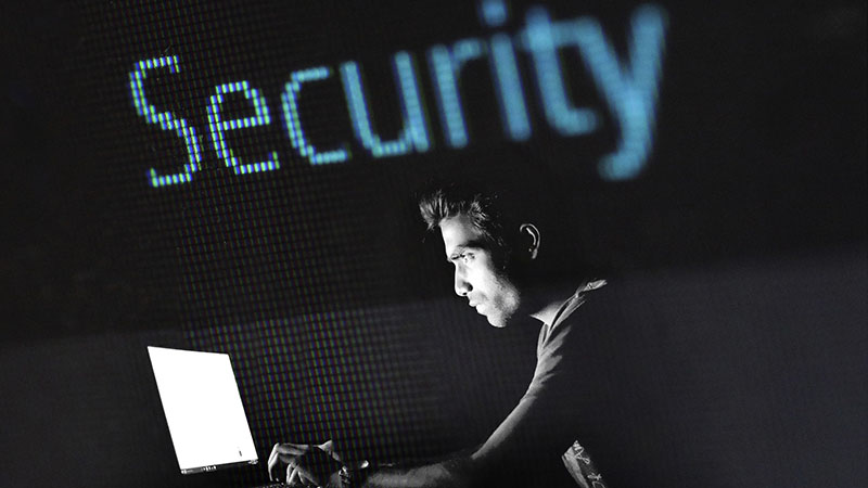 """A man working on a laptop with the word """"Security"""" above him."""