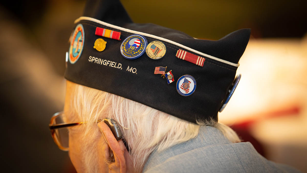 Man wearing hat with military pins.