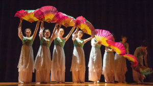 Women perform on stage with traditional fans.