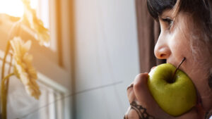 A woman biting on a green apple while looking out the window.