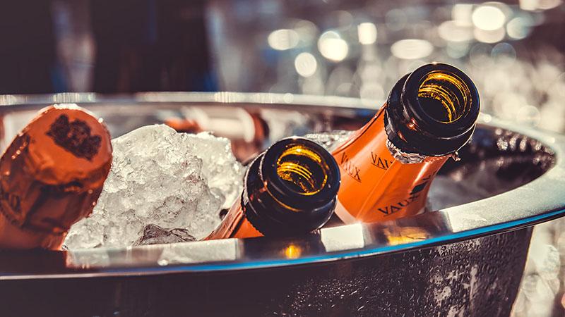Three bottles of beer in an ice bucket.