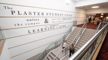 Two people walking down staircase in Plaster Student Union