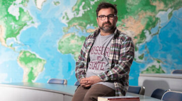 Man sits on desk in front of world map
