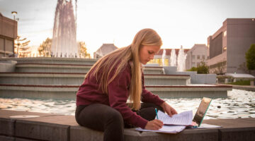 Woman does schoolwork by fountain