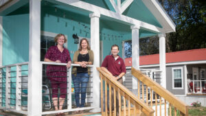 Krista Evans, Marnie Watson and David Rohall on porch of Eden Village home