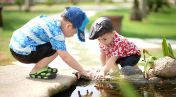 Two young children playing together outdoors.
