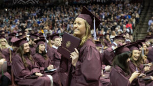 Girl in cap and gown holding up diploma.