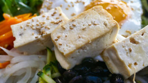 A plate of tofu and assortment of vegetables.